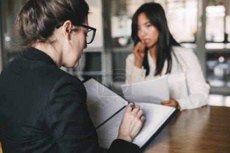 Photo pour Photo de l'arrière de la femme d'affaires grave interviewer et parler avec personnel féminin tendu au cours de l'entrevue d'emploi - business, le concept de carrière et de placement - image libre de droit