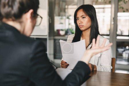 Photo pour Image de sérieuse femme asiatique à la recherche et de parler à la femme d'affaires tout en restant assis à table dans le bureau au cours de l'entrevue d'emploi - entreprise, la notion de carrière et de recrutement - image libre de droit