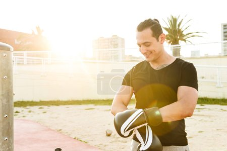 Photo of strong handsome young sportsman boxer wearing gloves outdoors looking aside.