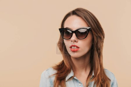 Image of pretty young serious woman wearing sunglasses standing isolated over beige background wall looking aside.