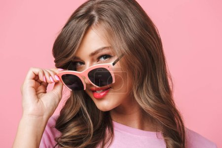 Image closeup of european woman 20s with long curly hairstyle looking at camera with beautiful smile from under fashionable sunglasses isolated over pink background