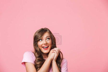 Photo pour Gros plan photo de joyeux jolie femme avec de longs cheveux bruns bouclés regardant de côté l'espace de copte et tenant les mains ensemble dans se réjouir isolé sur fond rose - image libre de droit