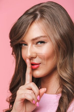 Image closeup of young beautiful woman 20s having long curly hairstyle smiling while holding finger at mouth with secret isolated over pink background