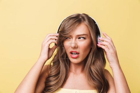 Photo of disappointed caucasian woman 20s with long brown hair expressing outrage and dislike while listening to music via headphones isolated over yellow background