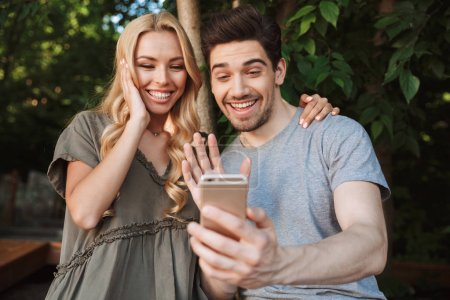Excited young couple taking a selfie together while standing at a city park