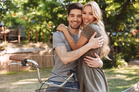Smiling lovely young couple posing together with bicycle and looking at the camera outdoors