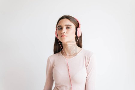 Portrait of a pretty young brunette girl listening to music with earphones isolated over white background