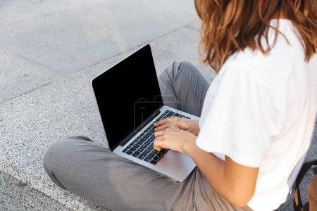 Photo pour Vue latérale d'une jeune femme tapant sur un ordinateur portable assis à l'extérieur - image libre de droit