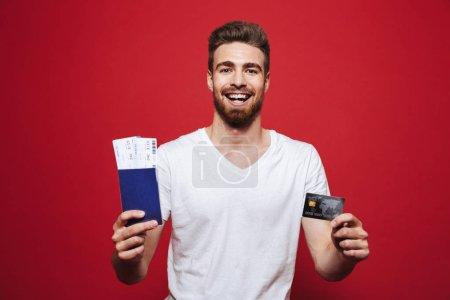 Foto de Retrato de un pasaporte de celebración alegre joven barbudo con entradas y con tarjeta plástico aislado sobre fondo rojo - Imagen libre de derechos