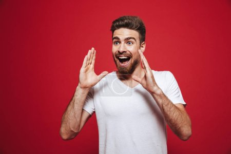 Portrait of an excited young bearded man screaming loud with arms at his face isolated over red background