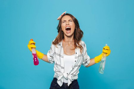 Photo for Image closeup of unhappy woman 20s in yellow rubber gloves for hands protection yelling while holding two detergent sprayers during cleaning isolated over blue background - Royalty Free Image