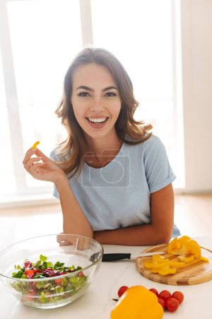 Photo for Satisfied young woman eating salad while sitting at the kitchen table - Royalty Free Image