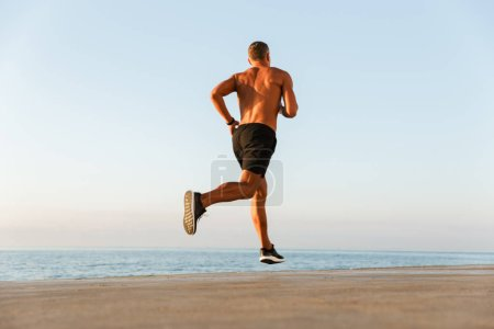 Back view of a shirtless sportsman with earphones running at the beach