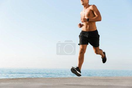 Photo pour Image recadrée d'un sportif torse nu courant sur la plage - image libre de droit