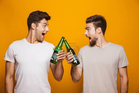 Photo for Portrait of a two cheerful young men best friends toasting with beer bottles isolated over yellow background - Royalty Free Image