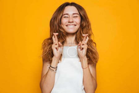 Photo for Portrait of an excited young girl holding fingers crossed for good luck isolated over yellow background - Royalty Free Image