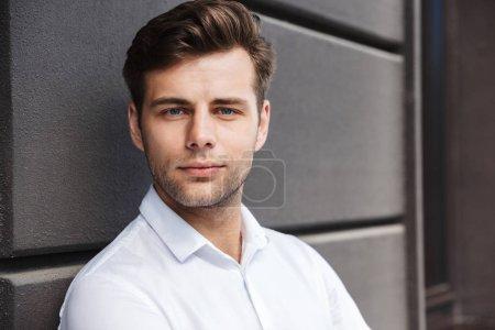 Photo pour Portrait d'un jeune homme habillé formel confiant appuyé sur un mur à l'extérieur regardant la caméra - image libre de droit