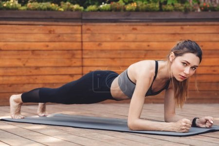 Portrait of a confident young fitness girl doing plank exercise on a mat outdoors