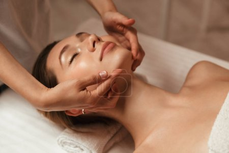 Photo for Young woman getting spa treatment with head massage at a spa center - Royalty Free Image