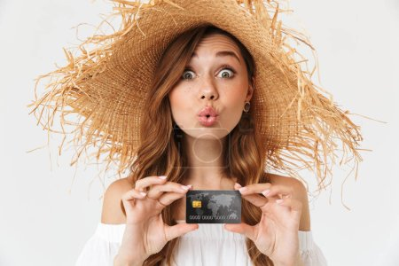 Photo for Portrait of cheerful young woman 20s wearing big straw hat rejoicing while holding credit card isolated over white background - Royalty Free Image