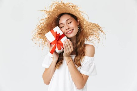 Photo of cute lovely girl 20s wearing big straw hat smiling and holding gift box with red ribbon isolated over white background