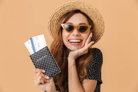 Charming brunette woman 20s wearing straw hat and sunglasses rejoicing while holding passport with travel tickets isolated over beige background