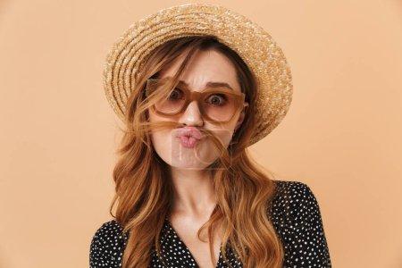 Photo pour Portrait de femme drôle amusante 20s portant chapeau de paille et lunettes de soleil s'amuser autour et mettre les cheveux comme une moustache isolé sur fond beige - image libre de droit