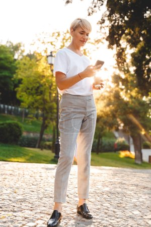Photo for Full length image of adult blond woman wearing casual clothing smiling while holding mobile phone and takeaway coffee during walk in green city park - Royalty Free Image