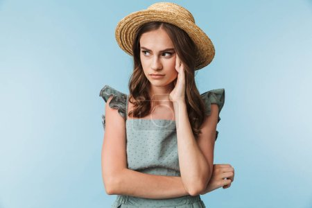 Photo for Close up portrait of a tired woman in dress and summer hat looking away isolated over blue background - Royalty Free Image