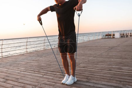 Photo pour Cropped image d'un jeune sportif, faire des exercices avec expandeur en bord de mer - image libre de droit