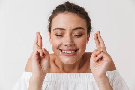 Photo pour Portrait d'une jeune femme brune décontractée heureuse tenant les doigts croisés pour bonne chance isolée sur fond blanc - image libre de droit