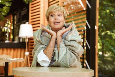 Photo pour Femme mûre excitée enveloppée dans une couverture relaxante alors qu'elle était assise dans un café - image libre de droit