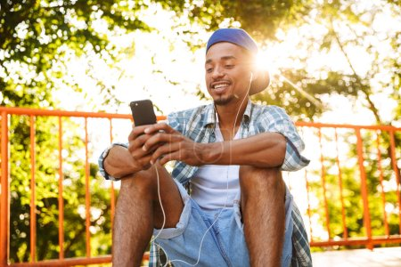 Happy young african man in earphones listening to music with mobile phone on a ramp at the skate park