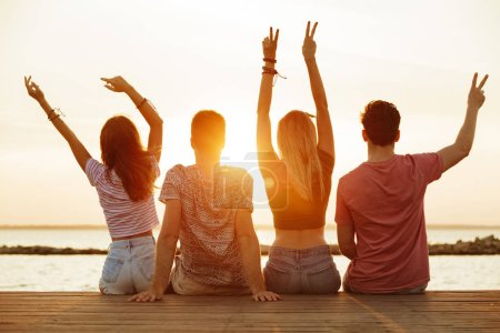 Back view photo of group of four friends loving couples walking outdoors on the beach showing peace gesture.