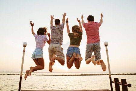 Back view image of group of four friends loving couples jumping outdoors on the beach.