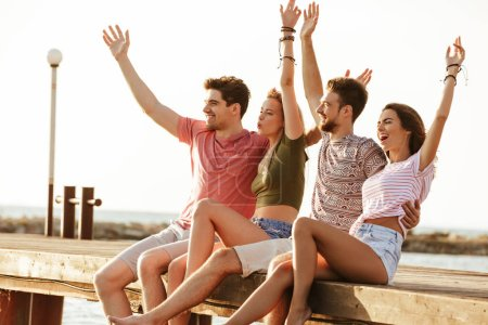 Picture of group of four friends loving couples sitting outdoors on the beach.