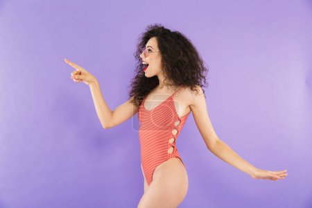 Photo for Portrait of a beautiful young woman dressed in swimsuit posing while standing isolated, pointing away - Royalty Free Image