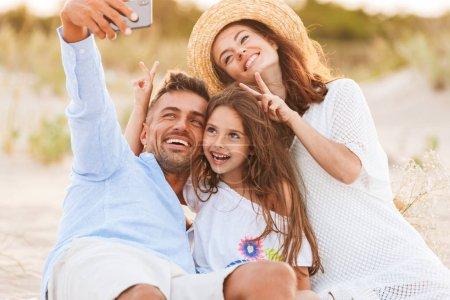 Photo pour Image de jeune mignon famille heureux s'amuser ensemble en plein air à la plage faire selfie par téléphone portable montrant le geste de paix. - image libre de droit