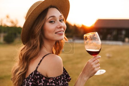 Photo for Image of cute pretty young woman outdoors holding glass drinking wine. - Royalty Free Image