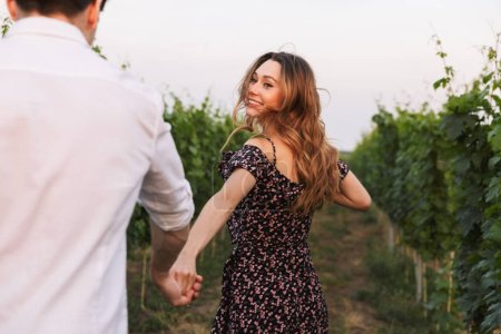 Romantic beautiful couple man and woman dating while walking outdoor together through vineyard on summer day