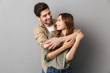 Photo for Portrait of a happy young couple hugging isolated over gray background - Royalty Free Image