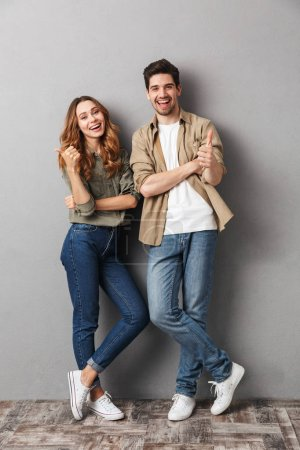 Photo for Full length portrait of a cheerful young couple standing together showing thumbs up isolated over gray - Royalty Free Image