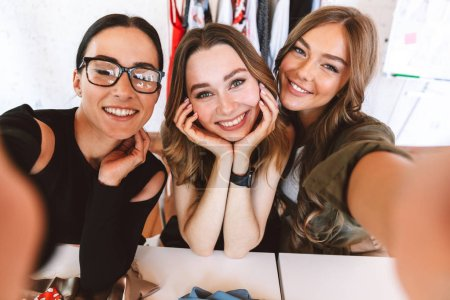 Three cheerful young women clothes designers working together at the atelier, sitting at the table and taking selfie