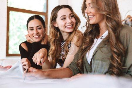Foto de Tres jóvenes diseñadoras de ropa sonrientes trabajando juntas en el taller, sentadas a la mesa - Imagen libre de derechos