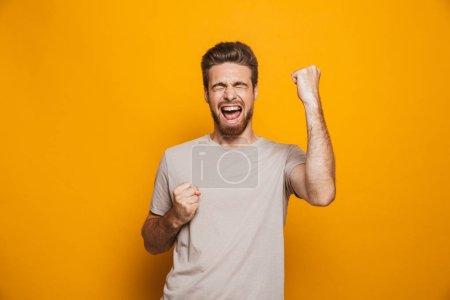 Photo pour Image de bel homme heureux permanent isolé au mur jaune backgroung faire un geste de vainqueur. - image libre de droit