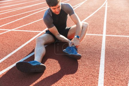 Photo pour Sportif fatigué souffrant d'une douleur à la cheville au stade - image libre de droit