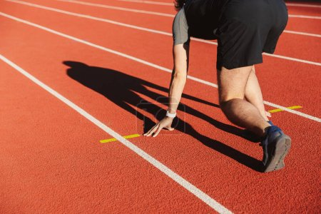 Photo for Motivated young sportsman getting ready to run at the stadium - Royalty Free Image