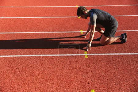Photo for Side view of motivated young sportsman getting ready to run at the stadium - Royalty Free Image