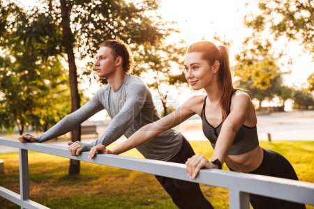 Photo of concentrated fitness sport loving couple friends in park outdoors make sport exercises.