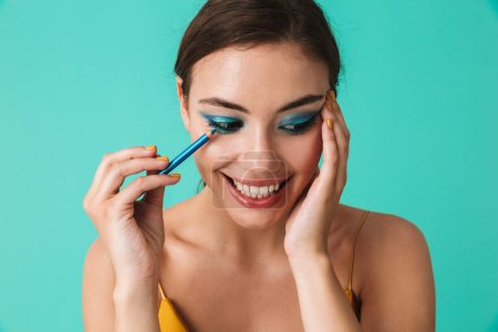 Close up portrait of a pretty young girl with bright make-up holding blue eye pencil isolated over blue